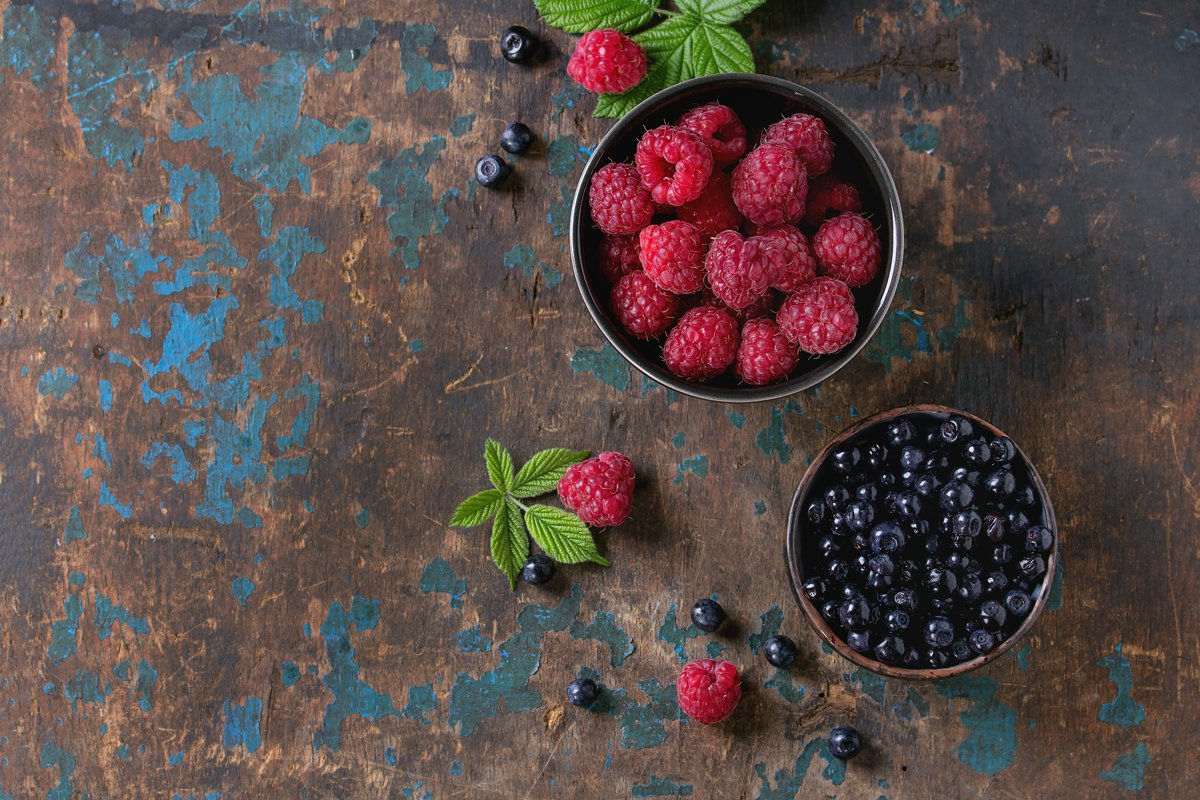 Bowls of raspberries and blueberries example image 1