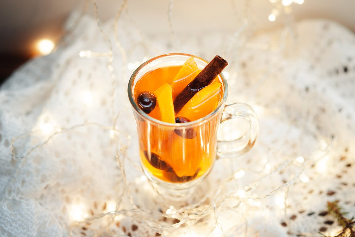 Homemade tea with citrus and cinnamon on a wooden table example image 1