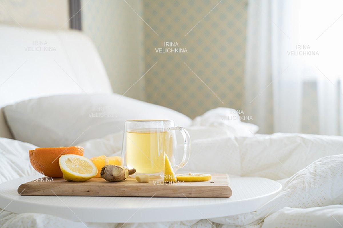 Cup of tea,orange,lemon,ginger in bed.Self treatment for flu example image 1