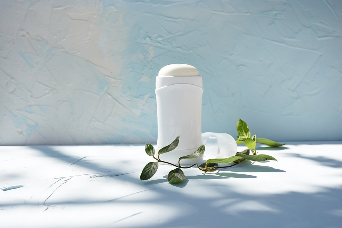 White bottle of dry deodorantat and green branch example image 1