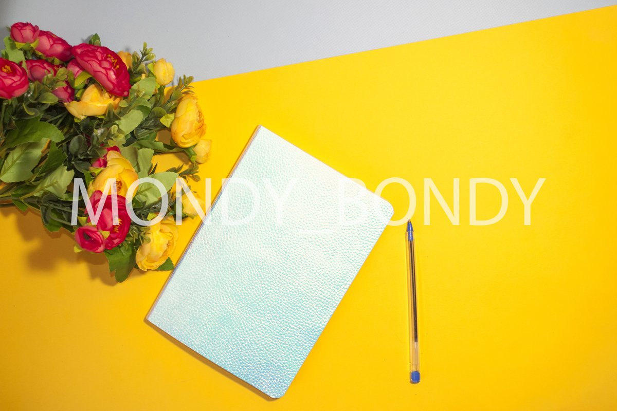 Flat lay. Holographic blue notebook and flowers on a colored example image 1