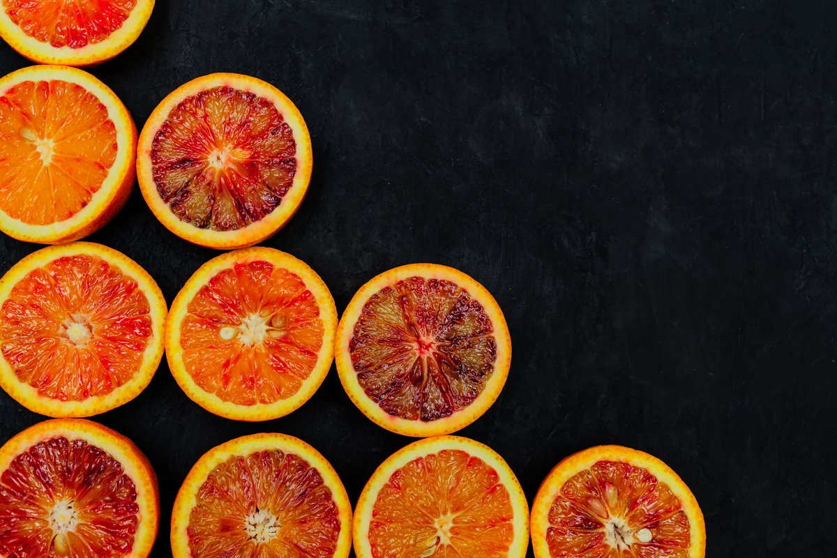 Organic Raw Red Blood Oranges in a rows on black background example image 1