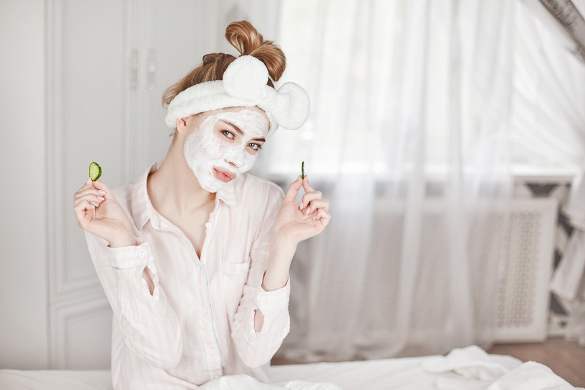 Girl with a face mask and slices of cucumber example image 1