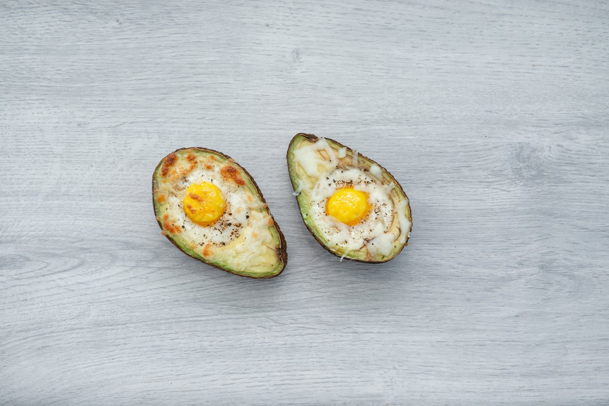 Two eggs baked in avocado on wooden table example image 1