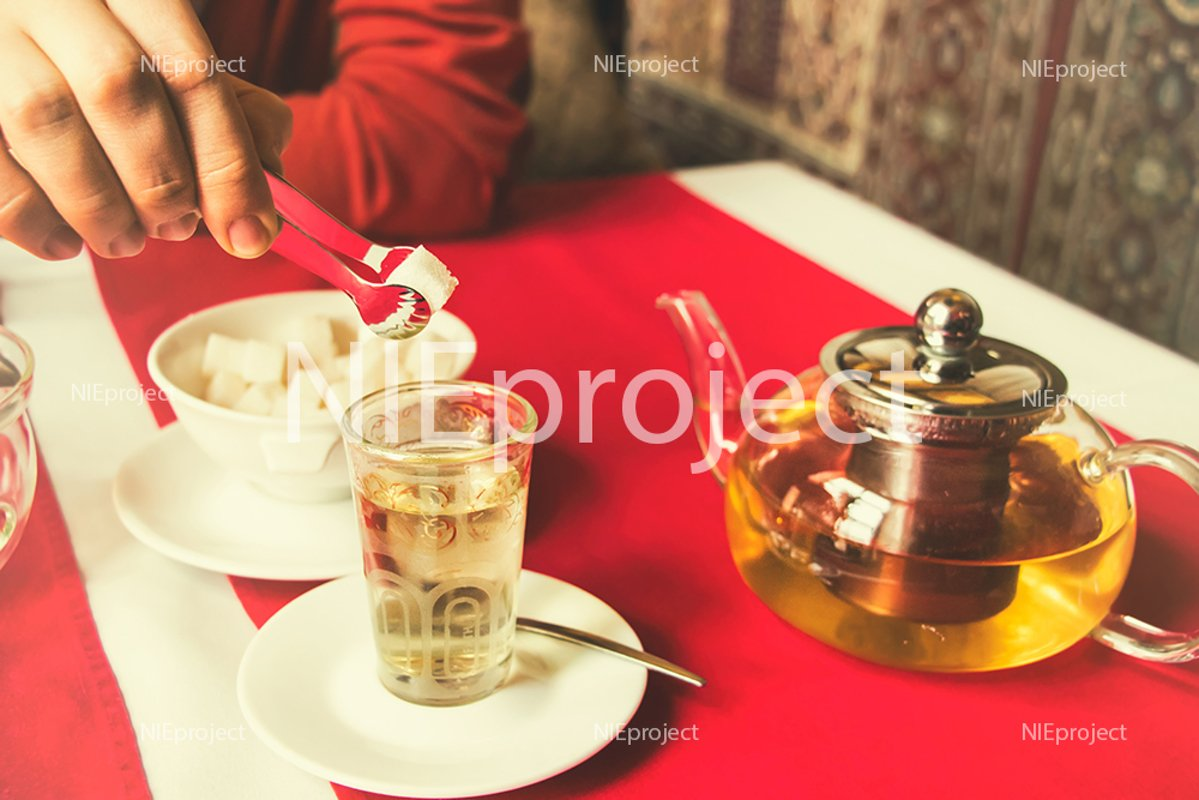 man puts a sugar cube in tea, restaurant, oriental style example image 1