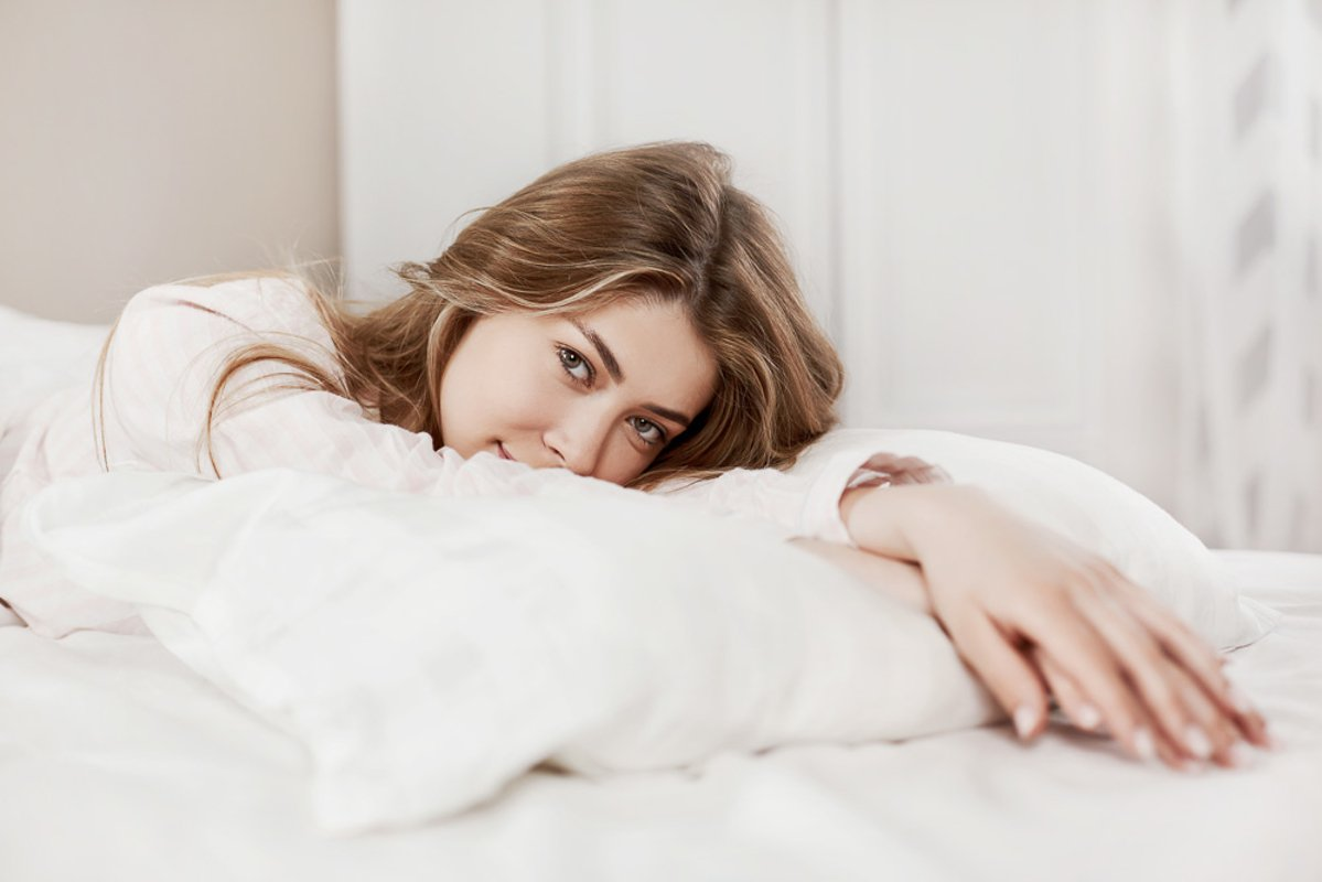 A charming girl luxuriates in bed after waking up. example image 1