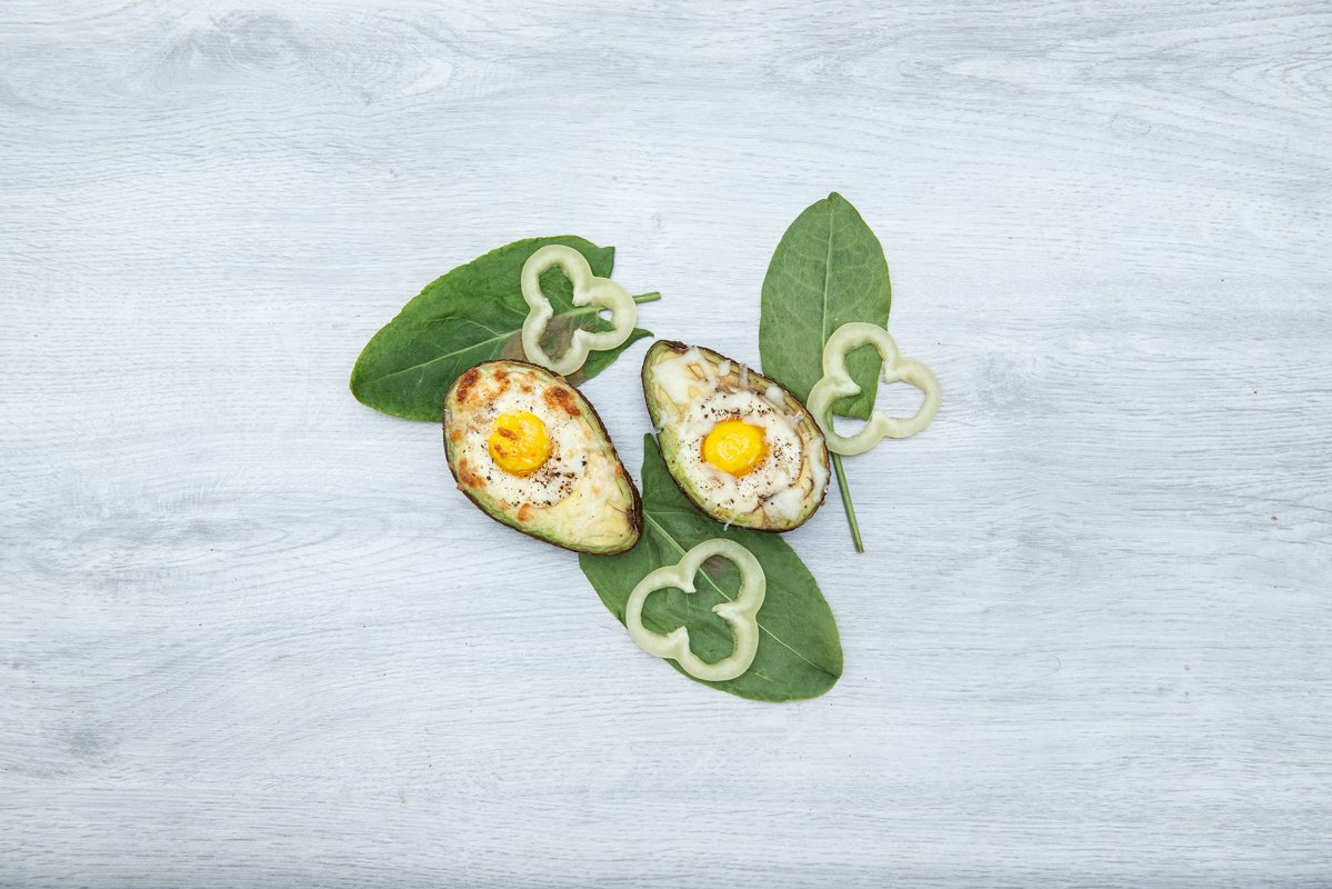 Two Eggs baked in avocado on wooden tabel and green leaves example image 1