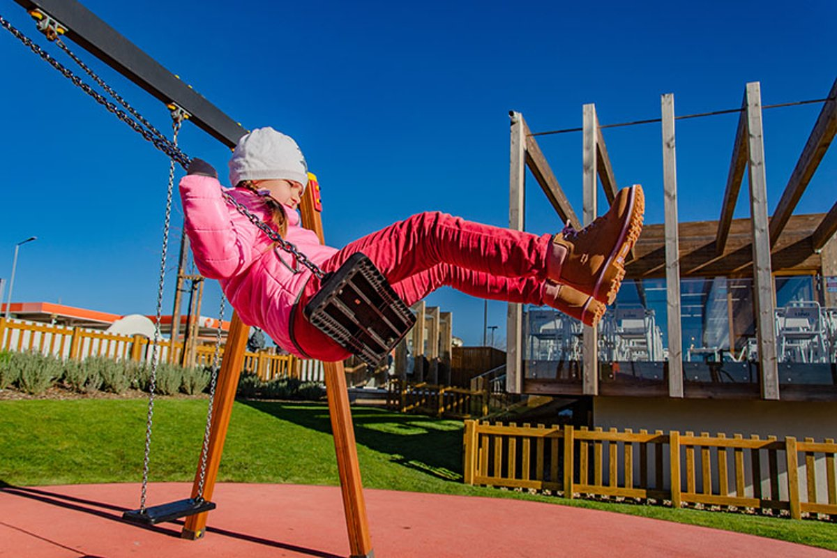 Little girl 5-6 years on a playground swinging on swing. example image 1