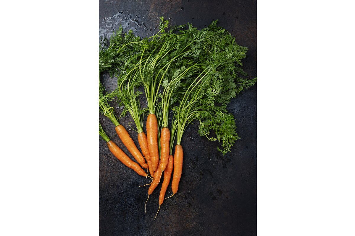 Fresh carrots with green leaves on the dark background example image 1