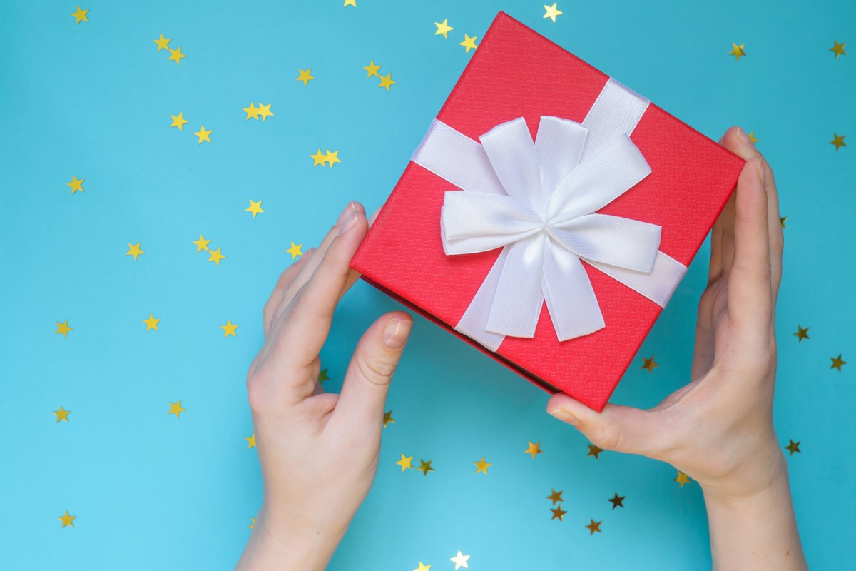 Woman opening red gift box on color blue background. example image 1