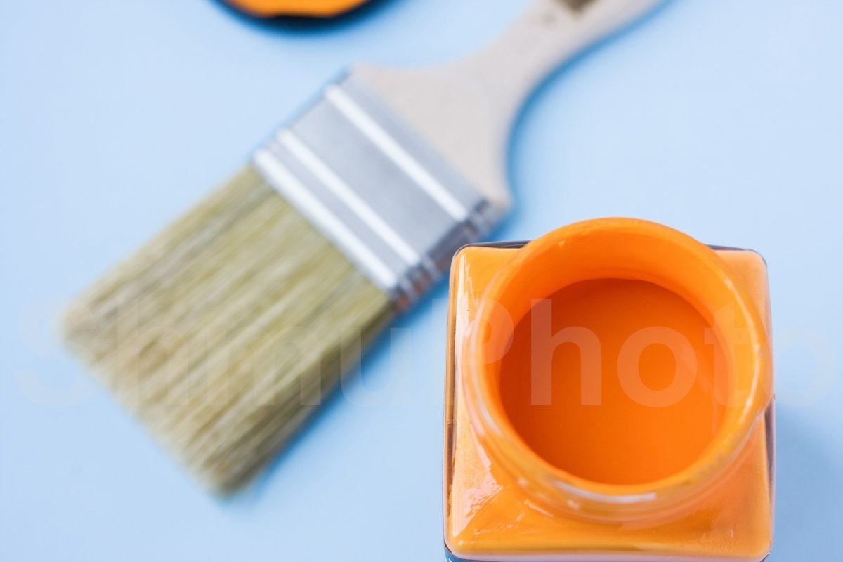 Glass can with orange paint against new brush on blue example image 1