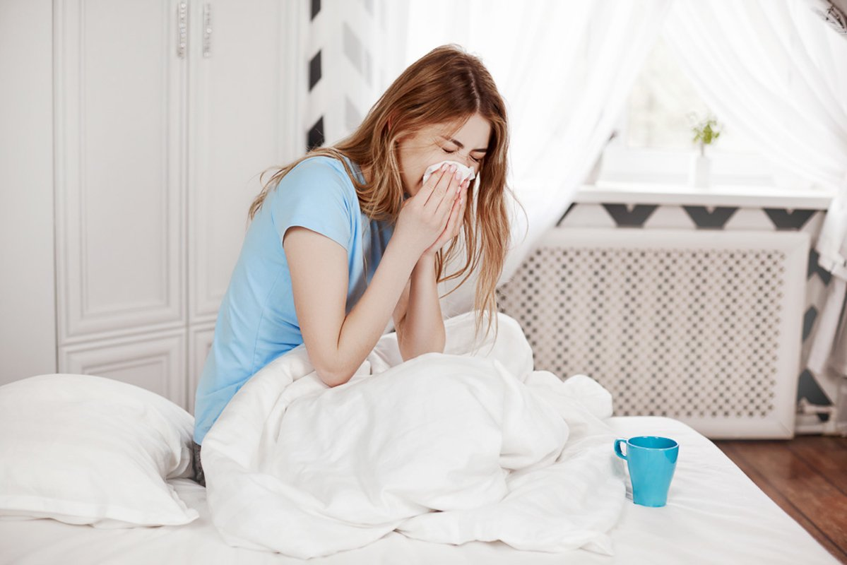 A young sick girl is sitting under a blanket on the bed example image 1