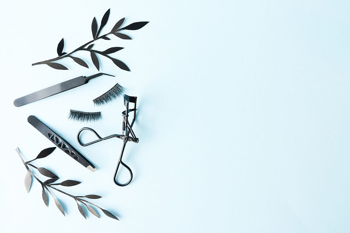 False lashes with black tweezers and paper leaves example image 1