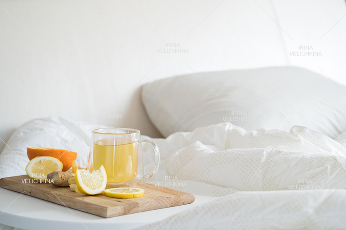 Cup of tea,orange,lemon,ginger in bed.Self treatment for flu example image 1