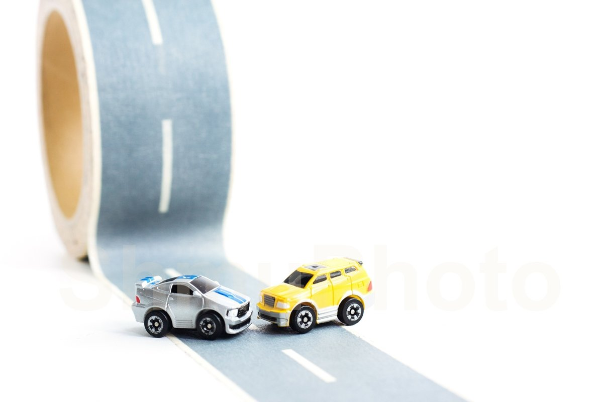 Cars accident on rough road. Two toy models on duct tape example image 1