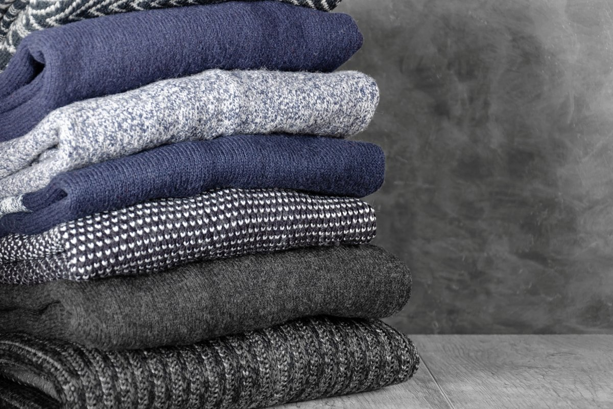 Stack of folded warm knitted men's sweaters example image 1