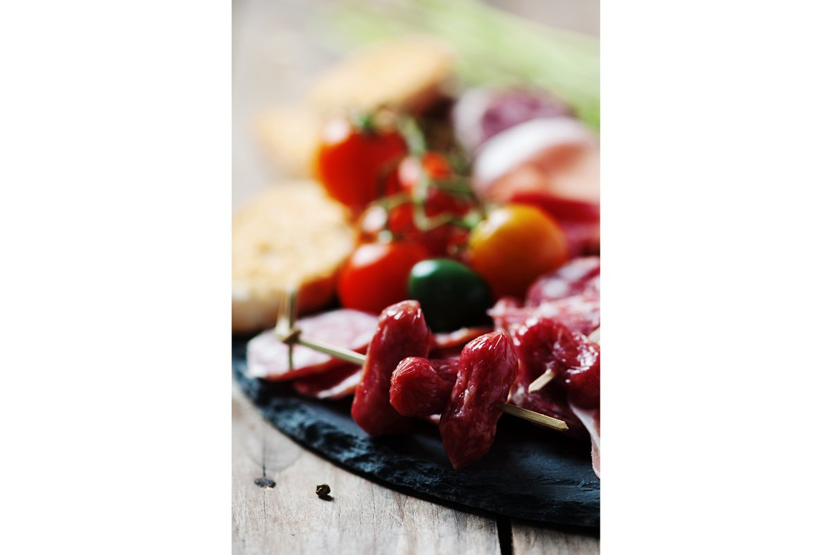Antipasto with ham, olive and tomato on the wooden table example image 1