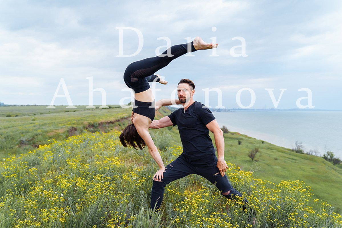 Couple practicing acro yoga poses outdoors outside. example image 1