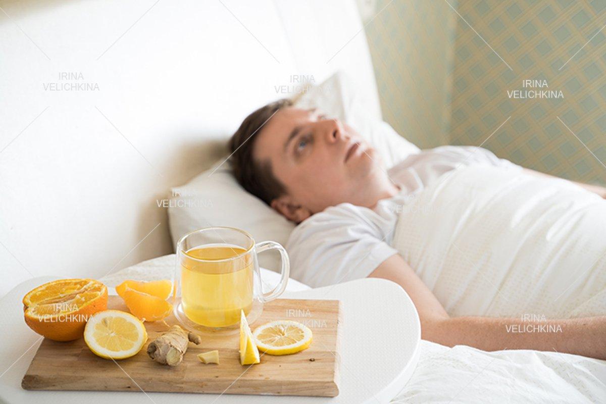 Sick man in bed. Cup of flu drugs. Tea, orange,lemon,ginger example image 1