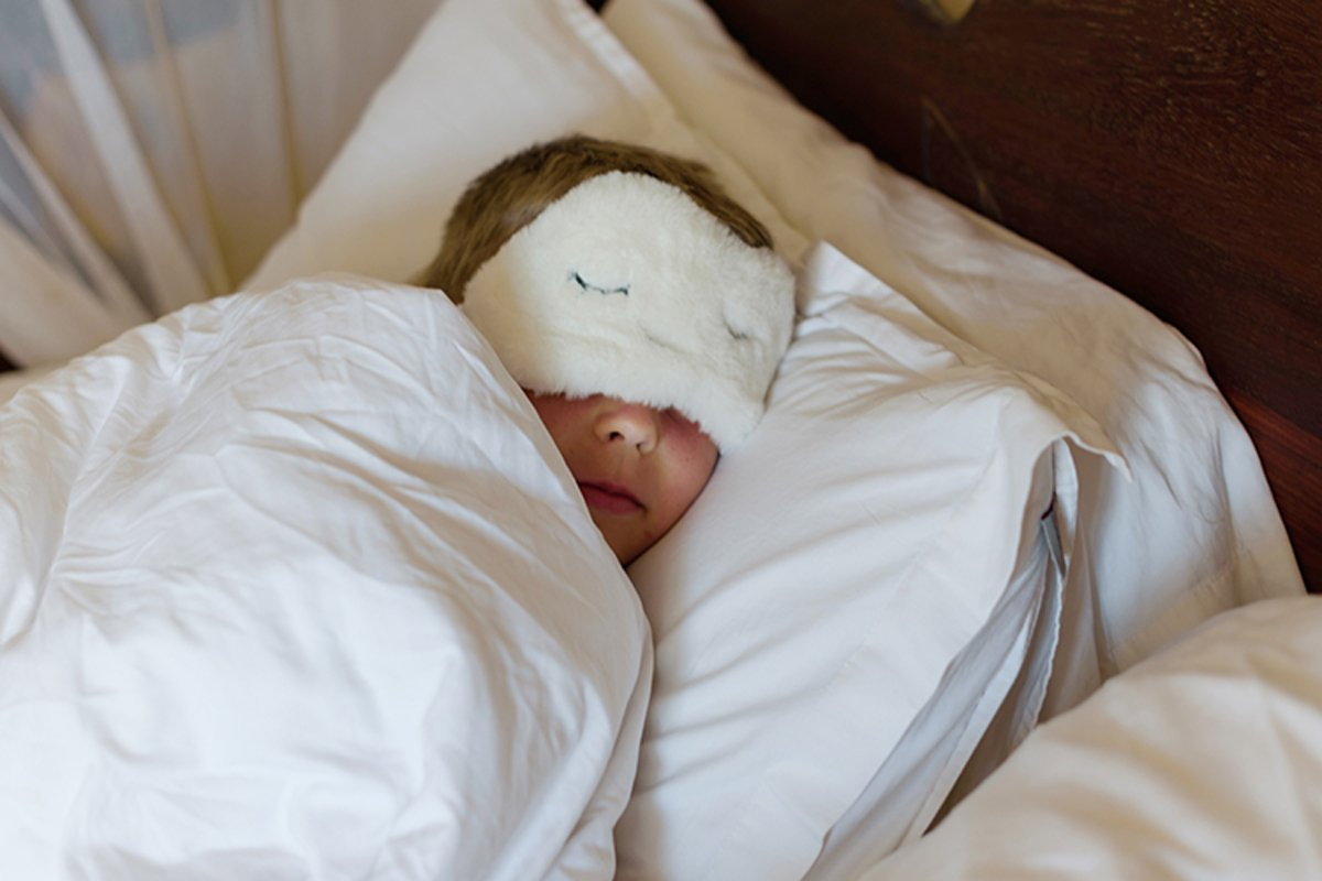 little boy in a sleep mask sleeps in a bed example image 1