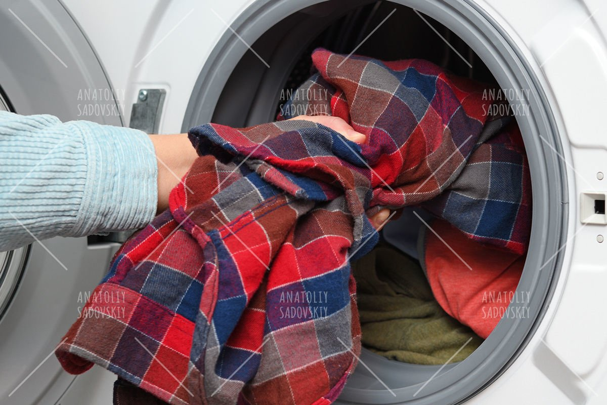 Woman puts clothes in washing machine example image 1