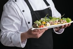 Chef in uniform serves a dish in a plate Product Image 1