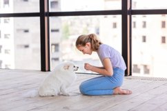 Cute teenage girl training her spitz dog at home Product Image 10