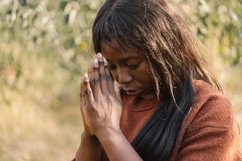 Afro girl closed her eyes while praying outdoors Product Image 1