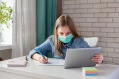 The masked girl is doing homework. Distance learning Product Image 1