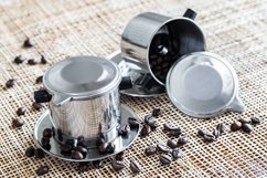 Two steel coffee makers with coffee beans on placemat. Product Image 1