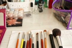 Makeup brushes and cosmetics on the table in beauty salon Product Image 1
