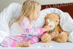 Little girl with teddy bear sitting on the bed Product Image 1