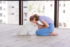 Cute teenage girl training her spitz dog at home Product Image 7