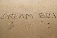 Handwritten DREAM BIG on a sandy sea beach Product Image 1