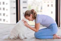 Cute teenage girl training her spitz dog at home Product Image 1