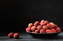 Fresh organic Lychee fruit in black plate. Product Image 1