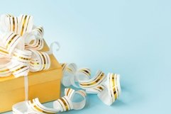 Golden gift box with golden ribbon on blue background Product Image 1