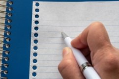 Hand writing with a white pen on page from blue notebook. Product Image 1