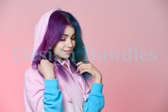 Girl listening to music on headphones on a pink background Product Image 3