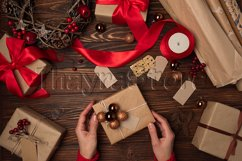 Female hands wrapping gift box on brown wooden table Product Image 1