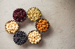 Variety of nuts and raisins in small bowls Product Image 1