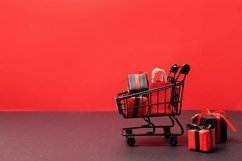 black paper bags and gift boxes in shopping cart on red Product Image 1