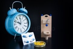 Wooden toy toilet, pills and alarm clock on black background Product Image 1