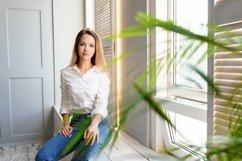 beautiful young girl sitting alone on the windowsill Product Image 1