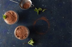Two servings of tiramisu garnished with cocoa and mint Product Image 1