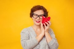 Elderly positive woman holds piggy bank on yellow background Product Image 1