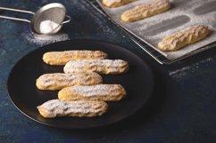 Savoyardi cookies sprinkled with powdered sugar on blue Product Image 1