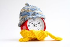 alarm clock in knitted hat and scarf. winter time concept Product Image 1