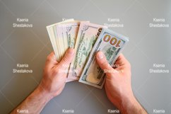 men's hands hold and count different American dollar bills Product Image 1
