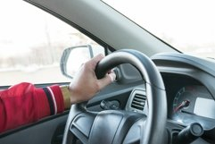 Men's hand on the steering wheel of a modern car Product Image 1